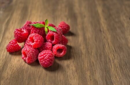 Fresh colorful organic raspberry fruit against wooden background.