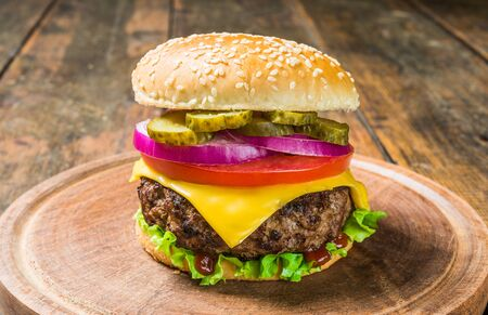 Cheese burger with cheese against wooden background. Tasty fast food. Stock Photo