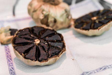 Close up of organic black garlic on display at a street food market. Stock Photo