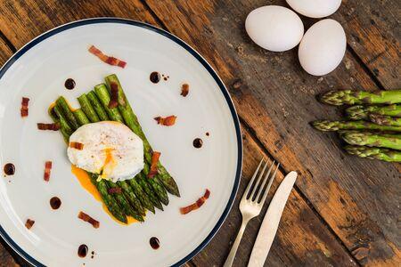 Fotografía de alimentos de un huevo escalfado con espárragos y tocino crujiente