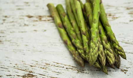 Close up of a bunch of asparagus against white wooden background.