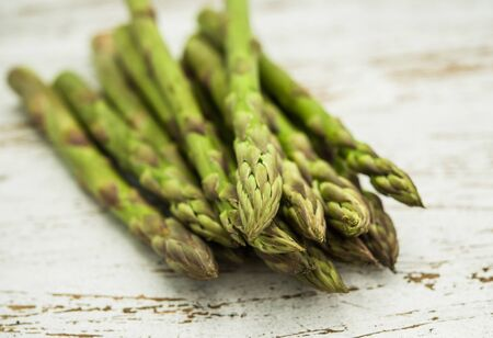Close up of a bunch of asparagus against white wooden background