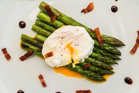 Photographie culinaire d'un œuf poché aux asperges et bacon croustillant.