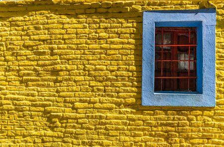 Bunte blaue Vintage Retro-Fenster und gelbe Backsteinmauer des alten Hausbaus.