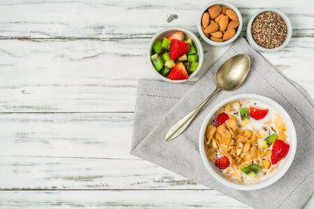 Bowl of breakfast cereals with milk, strawberry, kiwi, almonds, and seeds Stok Fotoğraf