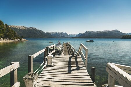Landscape photo with old wooden pier, transparent lake water, and mountains Zdjęcie Seryjne - 140613879