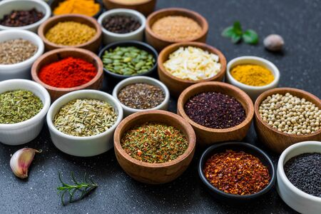 Variety of colorful spices, herbs, and seeds on black stone background