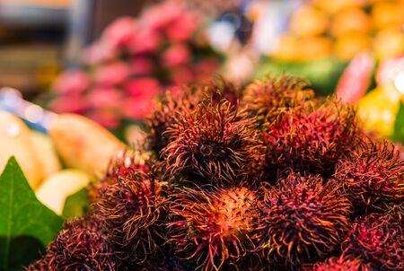 Close up food photo of organic rambutan exotic fruit at farmers market stall