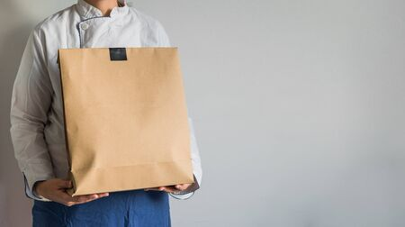 Chef making a delivery of food takeaway in a paper carton bag with copy space. Foto de archivo
