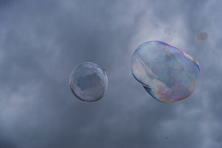 Big soap bubbles against the background of cloudy sky.