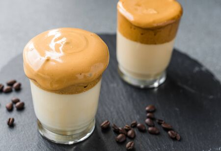 Dalgona coffee whipped cream mousse against grey background.