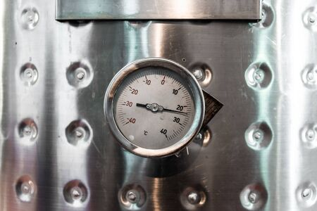 Thermometer on a steel wine tank for wine fermentation at a winery.