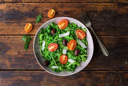 Salad bowl with arugula rocket salad, black olives, and cherry tomatoes