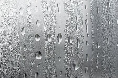 Macro photography water drops on glass window white background after the rain