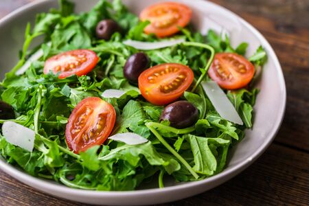 Salad bowl with arugula rocket salad, black olives, and cherry tomatoes