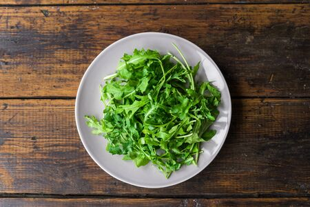Arugula rocket salad on a plate against wooden background