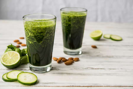 Spinach and almond smoothies against white wooden background. 免版税图像