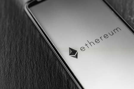 Logo of Ethereum blockchain money cryptocurrency on screen of smartphone. 免版税图像