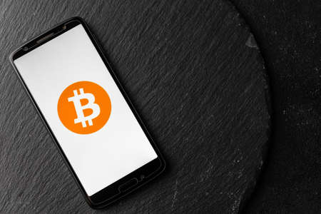 Logo of Bitcoin digital cryptocurrency money on the screen of a smartphone.