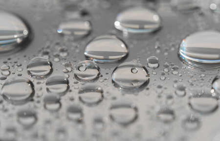 Macro photography of water drops on a mirror reflective surface.
