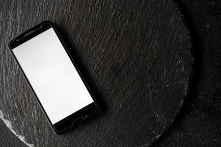 Empty screen of a smartphone with copy space against black slate background.