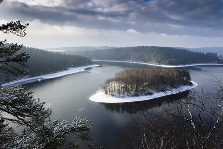winter weather: Heavy Clouds Winter Top View Landscape Lake with Island During Snow Weather Stock Photo