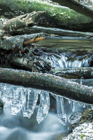 clear day in winter time: Icicles on Branch Over Frozen River. Long Time Exposure. Winter Landscape Detail.