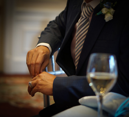 a groom in navy suite sits on a chair with wedding ring on his hand, and wine glass on a table on wedding day Stock Photo