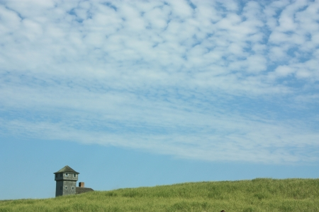 Old lighthouse by the sea with deep blue sky and green grass  Zdjęcie Seryjne