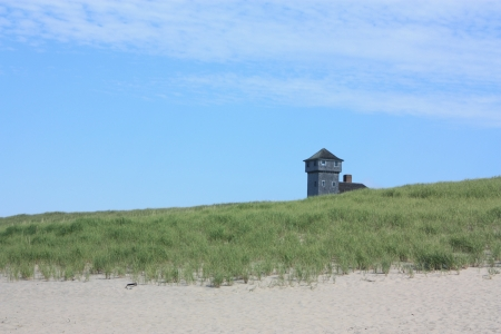 Old lighthouse by the sea with deep blue sky and green grass