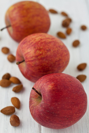 3 apples with almonds and hazelnuts on a white wooden background Stock Photo