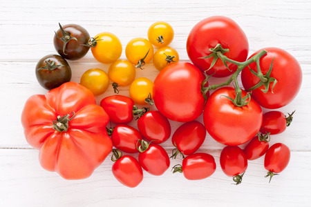 Colorful tomatoes on a white wooden board photo
