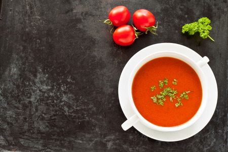 baking tray: Top view of a fresh tomato soup in a bowl on a rustic baking tray
