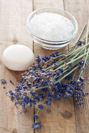 bath essence: Lavender flowers with soap and bath salt on a wooden table Stock Photo