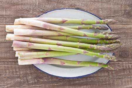 enamel: Bunch of fresh green asparagus on plate on enamel Stock Photo
