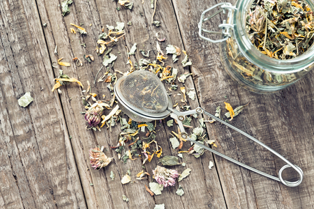 assam tea: Tea leaves with a tea strainer and a glass on a wooden table