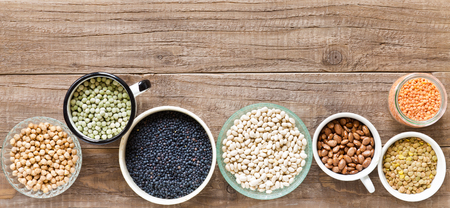 legumes: Various dried legumes in bowls on a wooden table