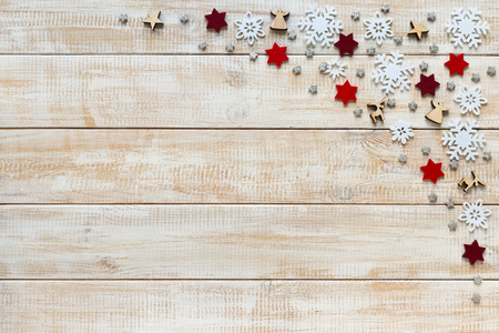 Christmas decoration with white snowflakes, red stars and wooden figures on a wooden background