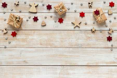 Christmas decoration with presents, snowflakes and stars on a wooden background