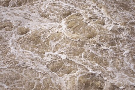 Stormy sea water, rough water surface. Foaming pink water. Foam and bubbles. Magnificence and power of nature concept. Foam pattern.