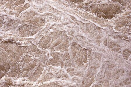 Abstrakter Hintergrund, raue Wasseroberfläche. Schäumendes rosa Wasser. Schaum und Blasen. Rosa Wasser, stürmisches Wasser. Pracht, Pracht und Kraft des Naturkonzepts. Schaummuster. Standard-Bild