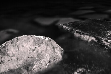 Black and white, monochrome, abstract, background, composition of two hearts submerged in water with visible texture. Blackness and atmosphere of calmness in rocky landscape. Rocks detail, close-up. Banco de Imagens