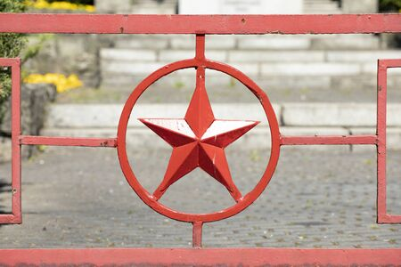Red metal star in circle. Red army star symbol forged in metal gate to Russian military cemetery. Katowice Poland