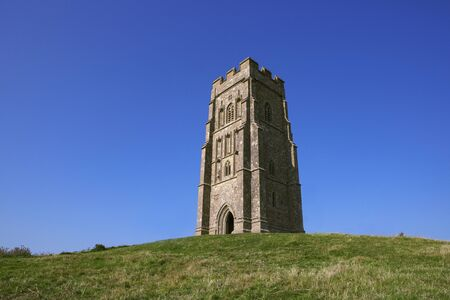 Top of Glastonbury Tor with St Michael's Tower. Somerset, England. Famous landmark. Historic english tower on the summit with blue sky, summer day. Beacon on hill. UK