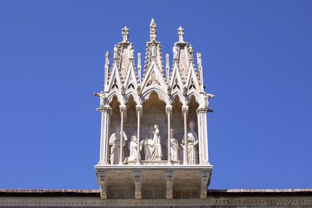 The sculpture of Holy Family over the entrance of the ancient Monumental Cemetery. Architectural detail above entrance to Camposanto Monumentale. Piazza dei Miracoli, Pisa, Tuscany, Italy. Blue sky. 免版税图像