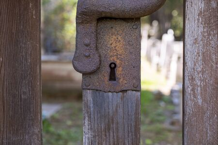 Rustic rusty keyhole. Old historic wooden gate with metal lock close up. Medieval, tarnished gate lock. Detail of old Middle Ages gate.