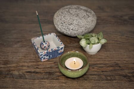Home altar. Burning candle in ceramic casing, incense sticks, stone and fresh plants. Mindfulness concept, meditation background. Zen Japanese style home altar. Relaxation technics. Minimalistic decor Stock Photo
