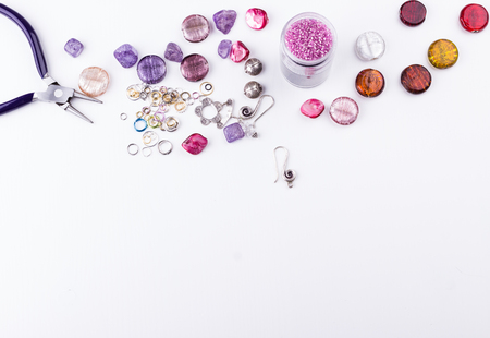 Glass seed and bugle beads, amethyst and turmaline stones, silver toggle, metal beads, shell rose beads, earings, metal rings and pliers on white background. Hobby, handmade,fine arts. Top view.