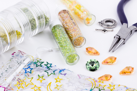 Jewelry making and beading process. Glass seed beads, beads, crystal stones, silver toggle, jewelry bag and pliers on white background. Selective focus.
