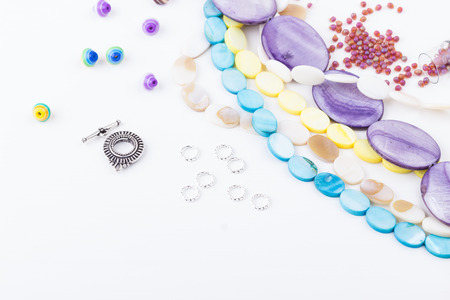 Glass and seed beads, gemstone beads, findings on white background. Selective focus.